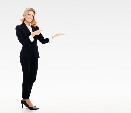Full body portrait of happy smiling young businesswoman, showing something or blank copyspace area for slogan or text message, on grey background, with blank copyspace area for text or slogan