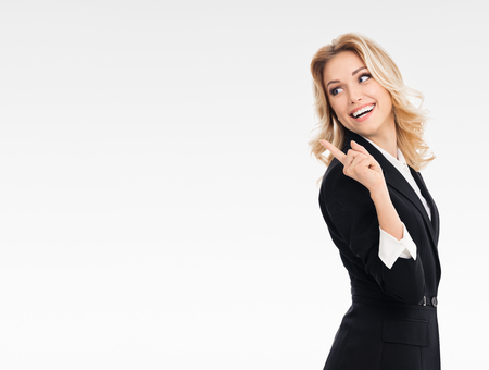 blondy: Portrait of happy smiling young cheerful businesswoman, showing something or blank copyspace area for slogan or text message, on grey background, with blank copyspace area for text or slogan