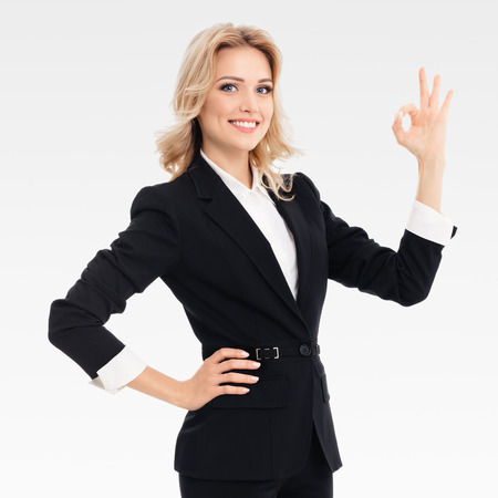 blondy: Happy smiling beautiful young businesswoman showing okay gesture, on grey background