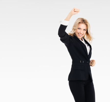 Happy gesturing young cheerful businesswoman, on grey background, with blank copyspace area for text or slogan