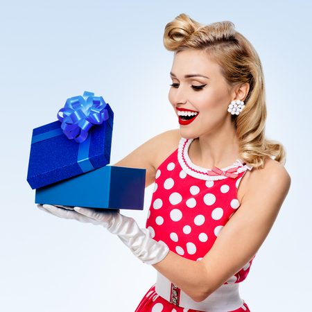 upsweep: Portrait of beautiful young happy woman dressed in pin-up style red dress in polka dot and white gloves, on blue background. Caucasian blond model posing in retro fashion studio shoot.