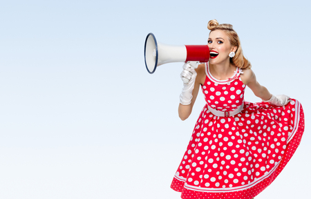 upsweep: Portrait of woman holding megaphone, dressed in pin-up style red dress in polka dot and white gloves, on blue background, with blank copyspace area for text or slogan. Caucasian blond model posing in retro fashion vintage studio shoot.