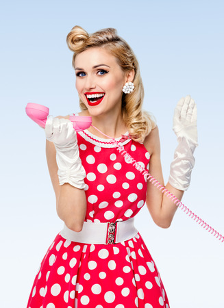 fifties: Funny portrait of beautiful happy woman with phone, dressed in pin-up style red dress in polka dot and white gloves, on blue background. Caucasian blond model posing in retro studio shoot.
