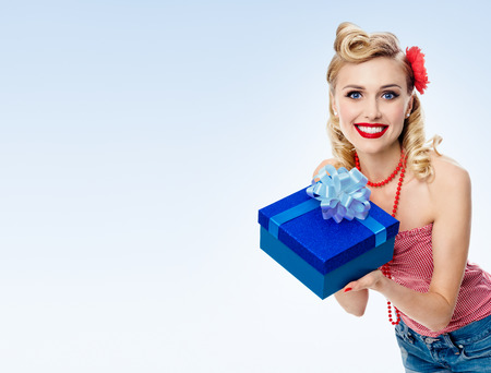 Portrait of beautiful young happy smiling woman in pin-up style clothing, on blue background, with blank copyspace area for text or slogan. Caucasian blond model posing in retro fashion and vintage concept studio shoot. Stock Photo