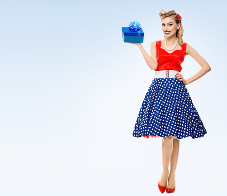 pinup: Full body portrait of smiling woman dressed in pin-up style dress with polka dot, on blue background, with blank copyspace area for text or slogan. Caucasian blond model posing in retro fashion and vintage concept studio shoot. Stock Photo