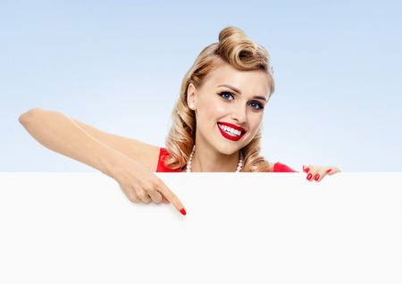 fifties: smiling blond woman in pin-up style dress, showing blank signboard with copyspace, on blue background. Caucasian blond model posing in retro fashion and vintage concept studio shoot.