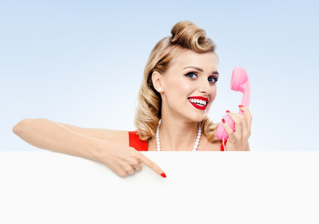 blank center: woman with phone, in pin-up style dress, showing blank signboard with copyspace area, on blue background. Caucasian blond model posing in retro fashion and vintage concept studio shoot. Stock Photo