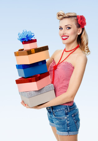 upsweep: Portrait of beautiful young happy smiling woman in pin-up style clothing, holding gift boxes, on blue background. Caucasian blond model posing in retro fashion and vintage concept shoot.
