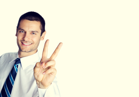 two persons only: Portrait of happy smiling businessman showing two fingers, or victory gesture, with blank copyspace area for slogan or text message Stock Photo