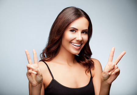 two person only: Beautiful young woman in black tank top clothing, showing two fingers or victory gesture, on bright grey background