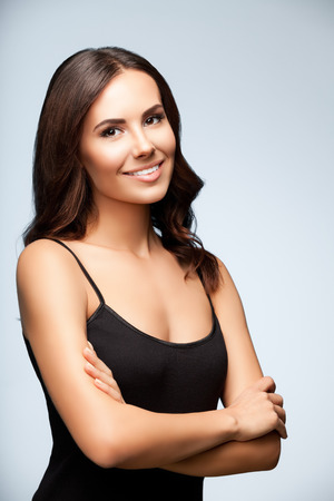 top clothing: portrait of beautiful smiling young woman in black tank top clothing, on bright grey background