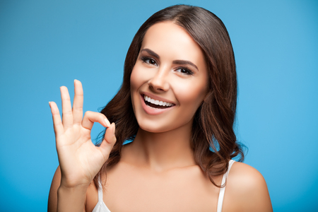 two persons only: Portrait of happy smiling young beautiful woman showing okay or zero hand gesture, over blue background