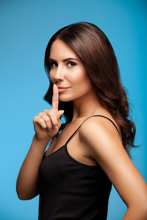 20s  closeup: portrait of beautiful young woman with finger on lips, on blue background Stock Photo