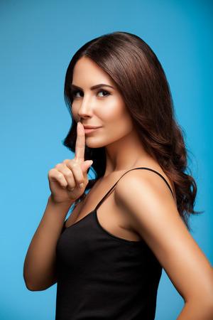guardar silencio: retrato de una mujer joven y bella con el dedo en los labios, en el fondo azul Foto de archivo