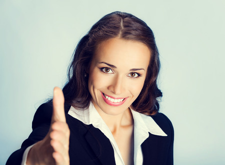 gestures: Portrait of young cheerful beautiful business woman giving hand for handshake Stock Photo