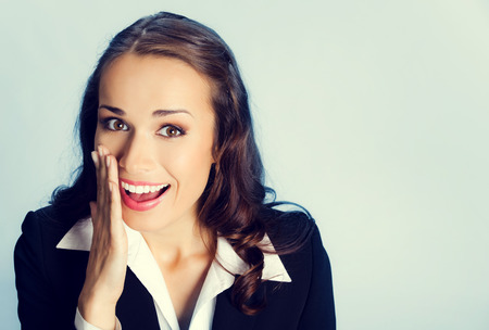 hearsay: Portrait of happy smiling young business woman covering with hand her mouth