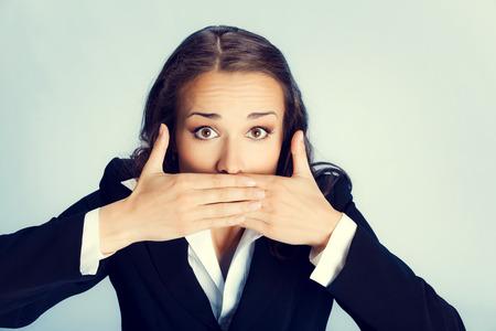 guardar silencio: Retrato de mujer sorprendida emocionada empresa joven con las manos cubriendo su boca, sobre fondo gris