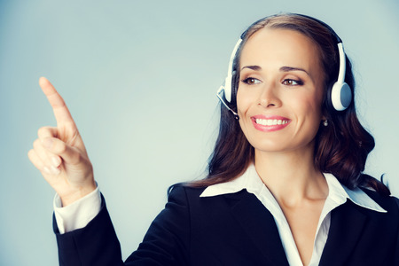 handsfree telephone: Portrait of happy smiling cheerful customer support phone operator in headset pointing at something Stock Photo