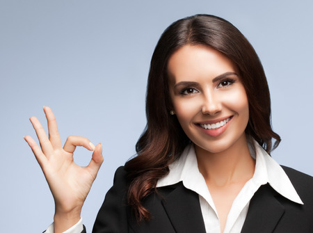 a ok: Portrait of happy smiling young businesswoman in black suit, showing okay gesture, over grey background Stock Photo