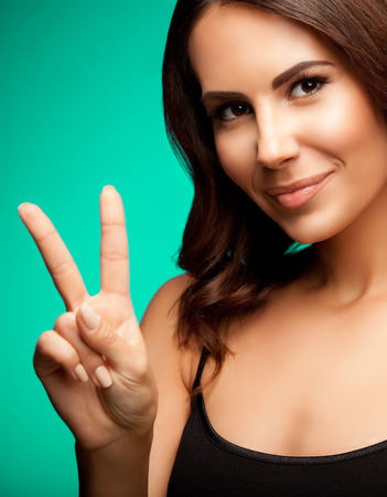 two persons only: Beautiful young woman in black tank top clothing, showing two fingers or victory gesture, on green background Stock Photo