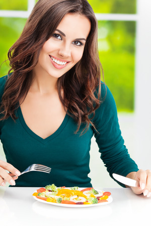 brunette woman: Portrait of happy smiling young brunette woman with vegetarian vegetable salad