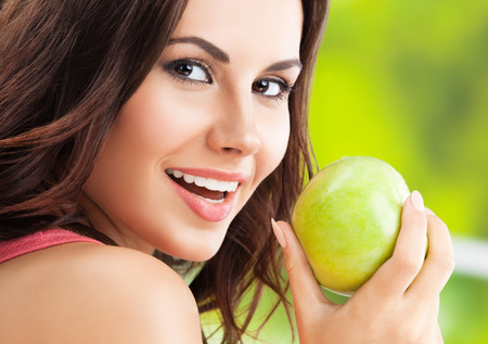 woman eat: Young happy smiling woman with green apple