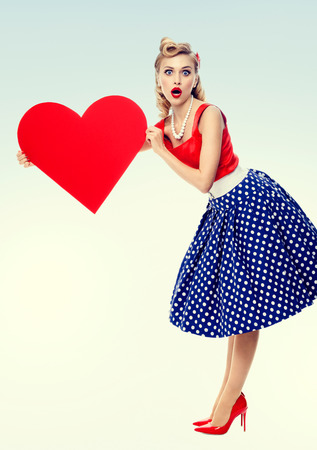 Full body of woman holding heart symbol, dressed in pin-up style dress with polka dot. Caucasian blond model posing in retro fashion and vintage concept studio shoot.