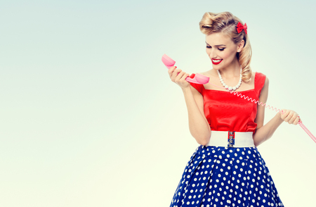 blank center: Funny portrait of beautiful woman with phone dressed in pin-up style dress in polka dot, with blank copyspace area for text or slogan. Caucasian blond model posing in retro fashion and vintage concept studio shoot. Stock Photo