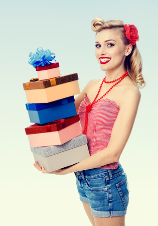 upsweep: Portrait of beautiful young happy smiling woman in pin-up style clothing, holding gift boxes. Caucasian blond model posing in retro fashion and vintage concept shoot.