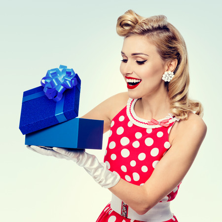 upsweep: Portrait of beautiful young happy woman dressed in pin-up style red dress in polka dot and white gloves. Caucasian blond model posing in retro fashion studio shoot.