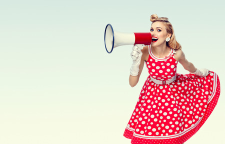 Portrait of woman holding megaphone, dressed in pin-up style red dress in polka dot and white gloves, with blank copyspace area for text or slogan. Caucasian blond model posing in retro fashion vintage studio shoot. Stock Photo