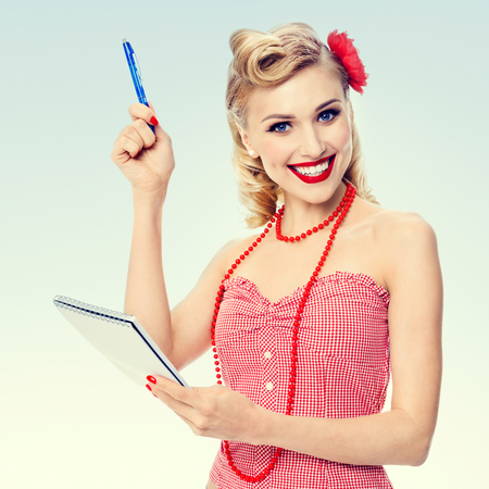 clothing model: Portrait of beautiful young happy smiling woman with notepad, in pin-up style clothing. Caucasian blond model posing in retro fashion and vintage concept studio shoot.