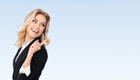 Office women: Portrait of happy smiling young cheerful businesswoman, showing something or blank copyspace area for slogan or text message, on blue background