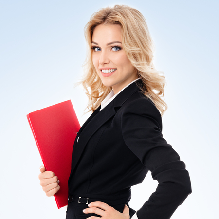 blondy: Portrait of young happy smiling businesswoman with red folder, on blue background Stock Photo
