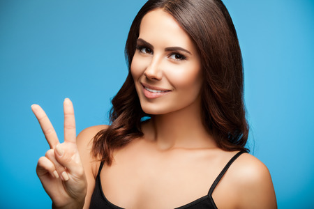 two persons only: Beautiful young woman in black tank top clothing, showing two fingers or victory gesture, on blue background Stock Photo