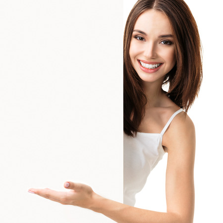 empty tank: Portrait of happy smiling young woman in white tank top casual smart clothing, showing empty blank signboard with copyspace area for text or slogan, isolated against white background