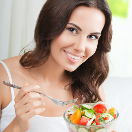 eating salad: Portrait of happy smiling young brunette woman with vegetarian vegetable salad, indoors. Healthy eating, beauty and dieting concept.