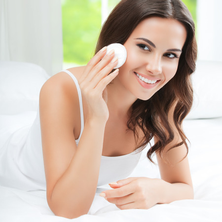 cotton pad: Portrait of happy smiling beautiful young woman cleaning skin by cotton pad, at home
