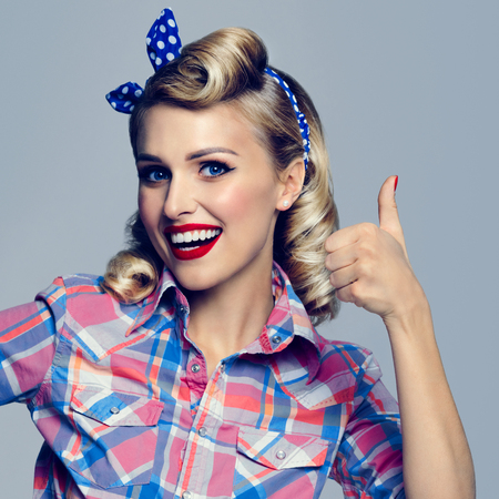 good grooming: Portrait of beautiful young happy smiling woman, showing thumb up gesture, dressed in pin-up style. Caucasian blond model posing in retro fashion and vintage concept studio shoot.