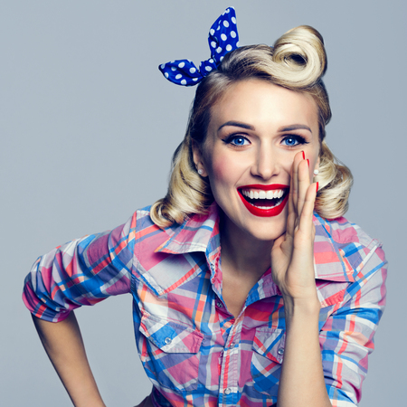 Portrait of beautiful young happy smiling woman, dressed in pin-up style. Caucasian blond model posing in retro fashion and vintage concept studio shoot.