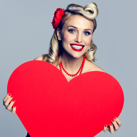 heart in hand: Portrait of beautiful young happy smiling woman holding heart symbol, dressed in pin-up style. Caucasian blond model posing in retro fashion and vintage concept studio shoot.