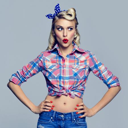 sorprendido: Retrato de la mujer sorprendida joven, vestida de estilo pin-up. Caucásica rubia modelo posando en la moda retro y disparar estudio del concepto de la vendimia.