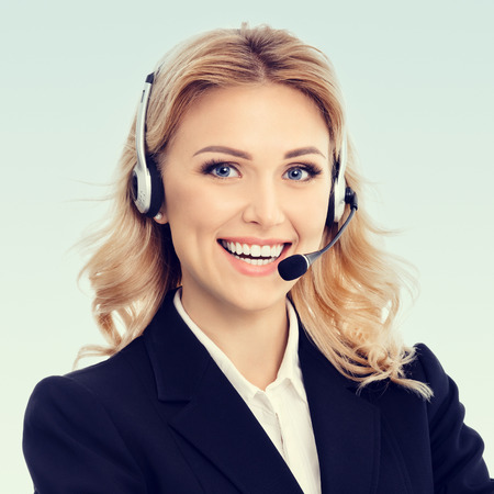 online service: Portrait of happy smiling young support phone operator or businesswomen in headset