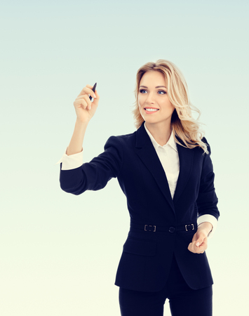 writing on glass: Happy smiling cheerful young businesswoman writing or drawing something on screen or transparent glass, by blue marker Stock Photo