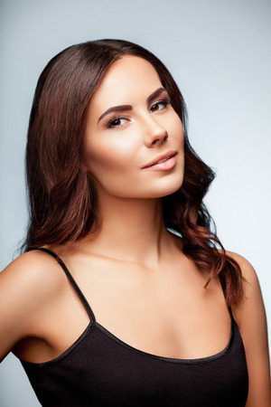 one person only: portrait of beautiful young woman in black tank top clothing, on bright grey background