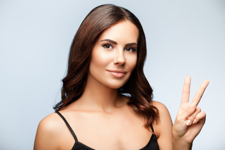 two persons only: Beautiful woman in black tank top clothing, showing two fingers or victory gesture, on bright grey background