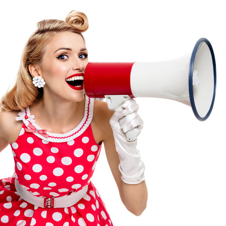 upsweep: Portrait of woman holding megaphone, dressed in pin-up style red dress in polka dot and white gloves, isolated on white background. Caucasian blond model posing in retro fashion vintage studio shoot.