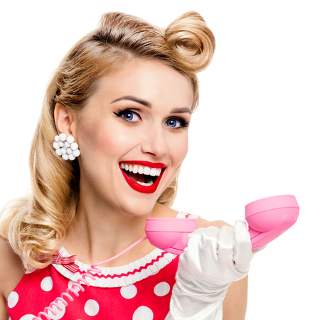 good grooming: Funny portrait of beautiful happy woman with phone, dressed in pin-up style red dress in polka dot and white gloves, isolated over white background. Caucasian blond model posing in retro studio shoot. Stock Photo