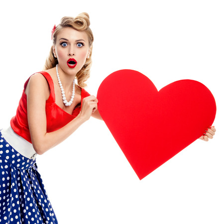 clothes pins: Woman holding heart symbol, dressed in pin-up style dress with polka dot, isolated over white. Caucasian blond model posing in retro fashion and vintage concept studio shoot. Stock Photo