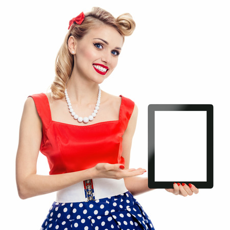 fifties: Woman, showing blank no-name tablet pc monitor, with copyspace, dressed in pin-up style dress in polka dot, isolated on white. Caucasian blond model posing in retro fashion vintage shoot.